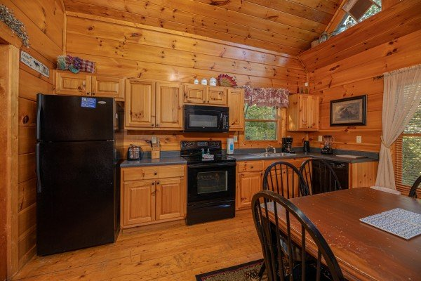 Dining space for six and kitchen with black appliances at Firefly Ridge, a 2 bedroom cabin rental located in Pigeon Forge