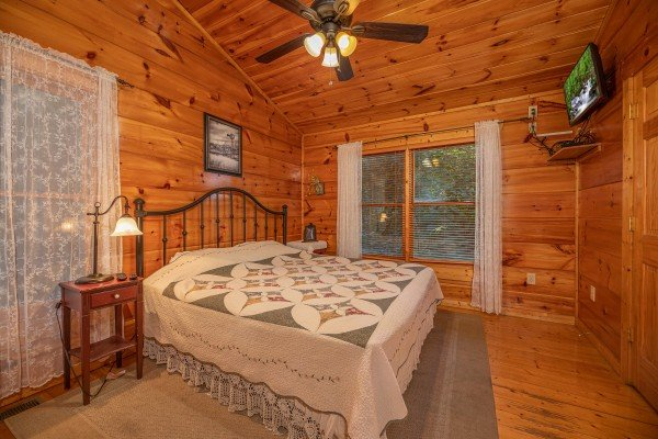Bedroom with a king bed and TV at Firefly Ridge, a 2 bedroom cabin rental located in Pigeon Forge