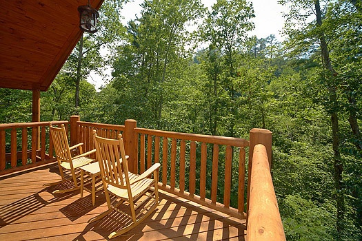 two rocking chairs on the second floor deck at cozy creek a 3 bedroom cabin rental located in pigeon forge