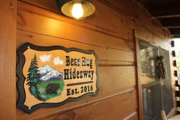 Custom welcome sign at Bear Hug Hideaway, a 1-bedroom cabin rental located in Pigeon Forge