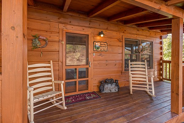 Front porch with rocking chairs at Bear Hug Hideaway, a 1-bedroom cabin rental located in Pigeon Forge