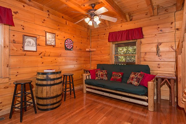 Futon and a dart board at Bear Hug Hideaway, a 1-bedroom cabin rental located in Pigeon Forge