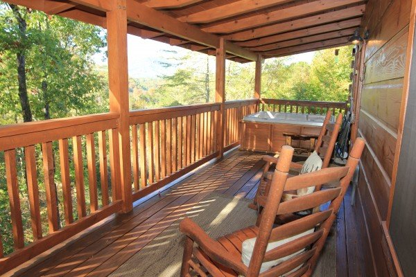 Rocking chairs and hot tub on a covered deck at Bear Hug Hideaway, a 1-bedroom cabin rental located in Pigeon Forge