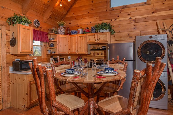 Kitchen with dining table and a stacked washer and dryer at Bear Hug Hideaway, a 1-bedroom cabin rental located in Pigeon Forge