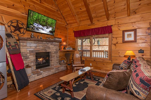 Stone fireplace with wall mounted television above at Bear Hug Hideaway, a 1-bedroom cabin rental located in Pigeon Forge