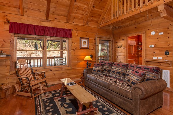 Brown sofa and rocking chair in the living room at Bear Hug Hideaway, a 1-bedroom cabin rental located in Pigeon Forge