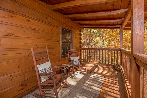 Rocking chairs on a covered deck at Bear Hug Hideaway, a 1-bedroom cabin rental located in Pigeon Forge