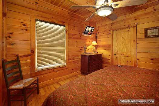 Dresser with TV above in main floor bedroom at Logged Out, a 3 bedroom cabin rental located in Pigeon Forge
