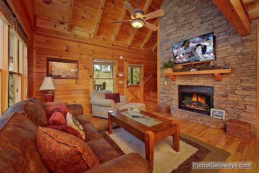 Living room with sofa bed by a stone fireplace at Logged Out, a 3 bedroom cabin rental located in Pigeon Forge