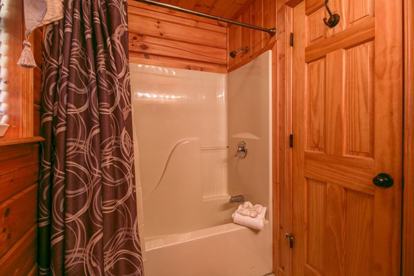 bathroom with tub and shower at a beary cozy escape a 1 bedroom cabin rental located in pigeon forge