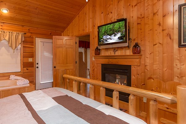 bedroom fireplace and television at a beary cozy escape a 1 bedroom cabin rental located in pigeon forge
