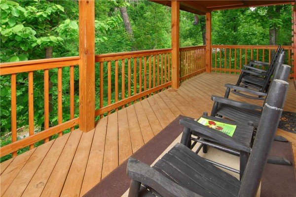 rocking chairs on a covered deck at a beary cozy escape a 1 bedroom cabin rental located in pigeon forge