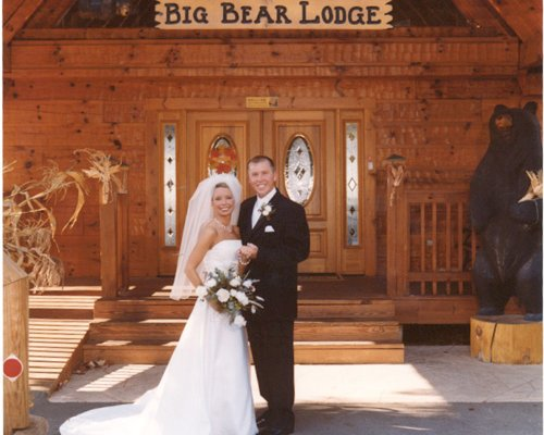 Newlyweds standing in front of Big Bear Lodge, a 7-bedroom cabin rental located in Gatlinburg