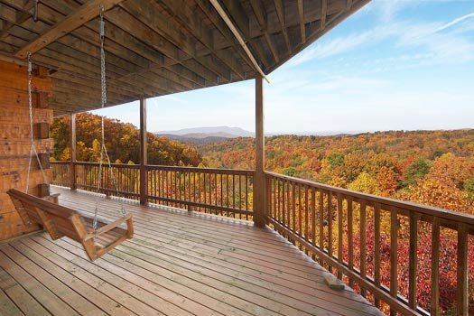 Swing on a covered deck overlooking the Smoky Mountains at Big Bear Lodge, a 7-bedroom cabin rental located in Gatlinburg