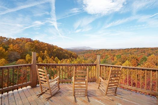 Three rocking chairs facing the Smoky Mountains at Big Bear Lodge, a 7-bedroom cabin rental located in Gatlinburg