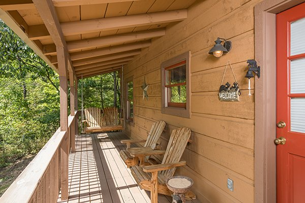Adirondack chairs and porch swing at the entry bearfoot adventure a 2 bedroom cabin rental located in gatlinburg