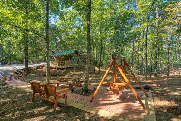 Outdoor space with a bench, picnic table, and log swing at Bearfoot Adventure, a Gatlinburg Cabin rental