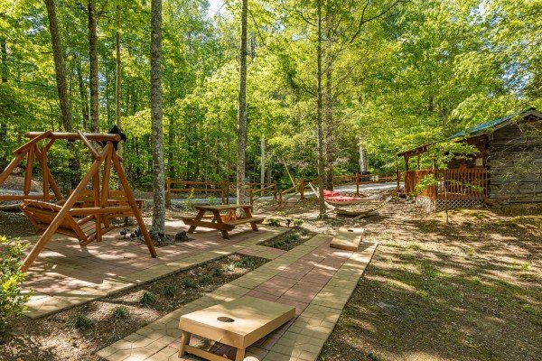 Cornhole, a swing, and a hammock on the patio at Bearfoot Adventure, a 2 bedroom cabin rental located in Gatlinburg