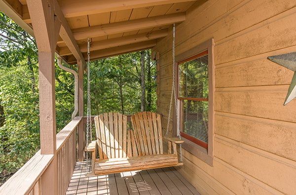 Porch swing on a covered deck at bearfoot adventure a 2 bedroom cabin rental located in gatlinburg