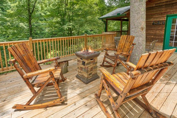 Fire pit and log rocking chairs on the deck at Kabbe Bear Cabin, a 1 bedroom cabin rental located in Gatlinburg