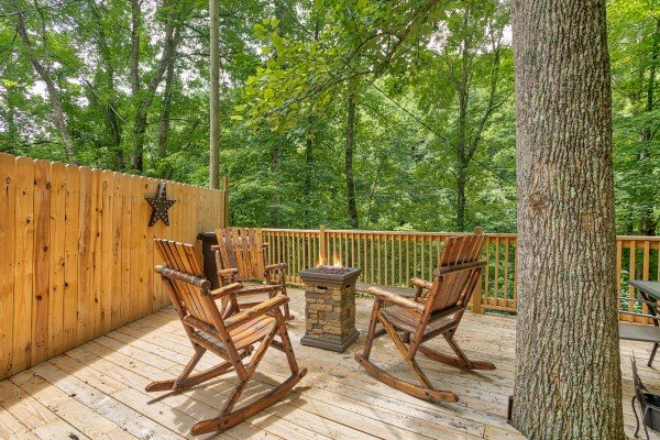 Fire pit on the deck with rocking chairs and a privacy fence at Kabbe Bear Cabin, a 1 bedroom cabin rental located in Gatlinburg