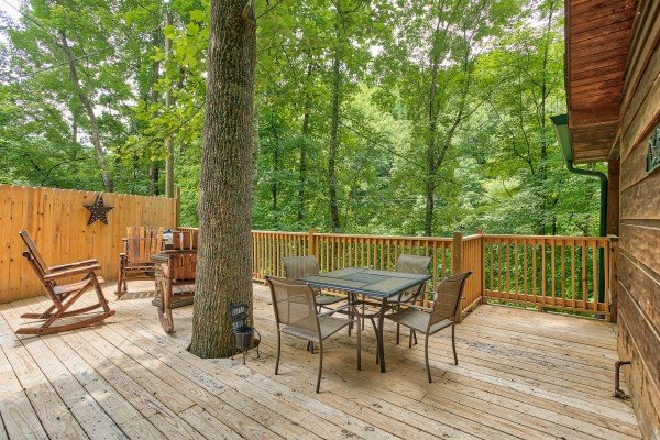 Deck with a fire pit, live tree, and dining space for four at Kabbe Bear Cabin, a 1 bedroom cabin rental located in Gatlinburg