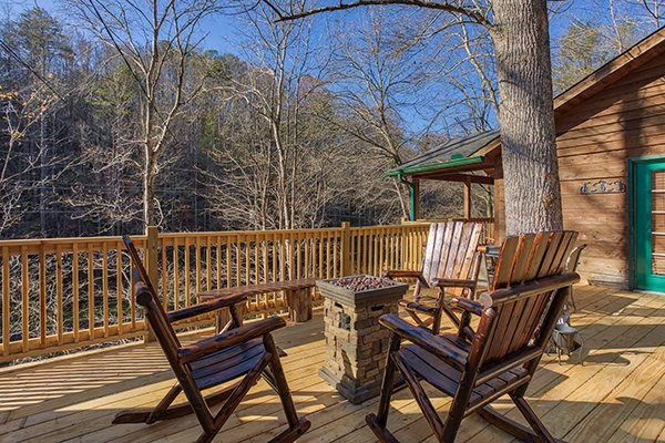 Fire pit and rocking chairs on the deck at Kabbe Bear Cabin, a 1 bedroom cabin rental located in Gatlinburg