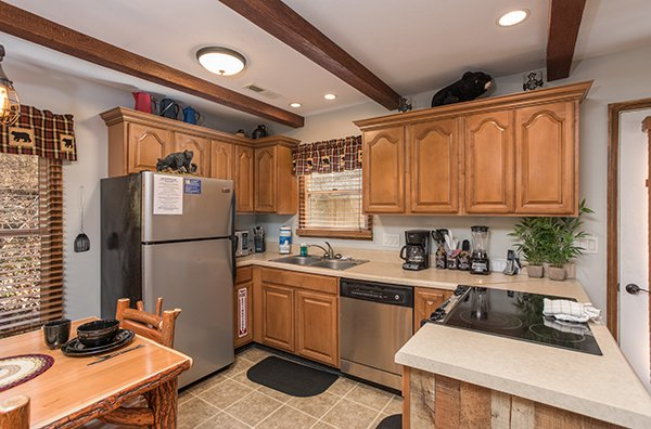 Kitchen with stainless appliances and dining space at Kabbe Bear Cabin, a 1 bedroom cabin rental located in Gatlinburg
