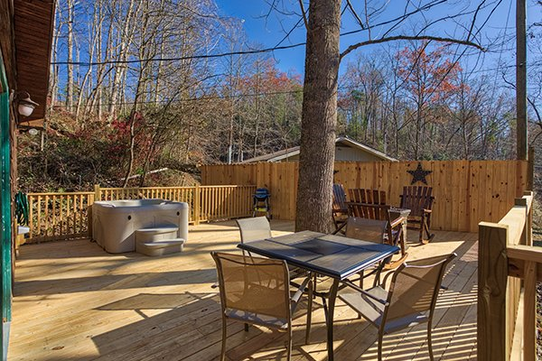 Large deck with dining set for four, rocking chair, bench, and hot tub at Kabbe Bear Cabin, a 1 bedroom cabin rental located in Gatlinburg