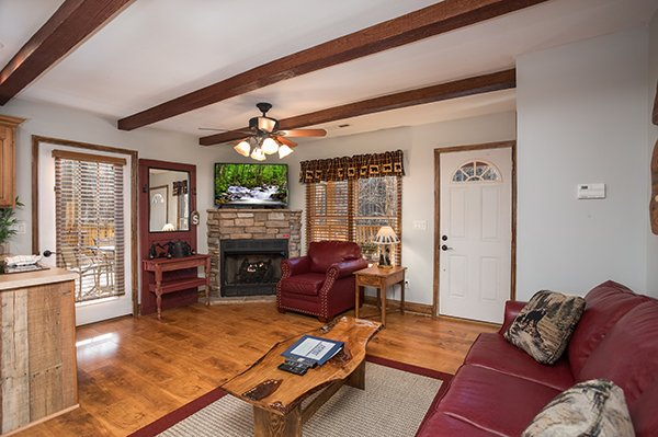Living room with a fireplace and TV at Kabbe Bear Cabin, a 1 bedroom cabin rental located in Gatlinburg