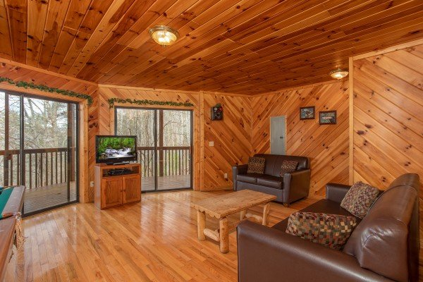 Game room with couch, loveseat, TV, and deck access at Angel's Place, a 2 bedroom cabin rental in Pigeon Forge