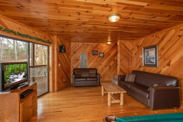 Game room with sofa, loveseat, TV, and deck access at Angel's Place, a 2 bedroom cabin rental in Pigeon Forge