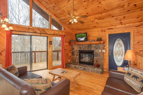 Living room with fireplace, TV, and deck access at Angel's Place, a 2 bedroom cabin rental in Pigeon Forge