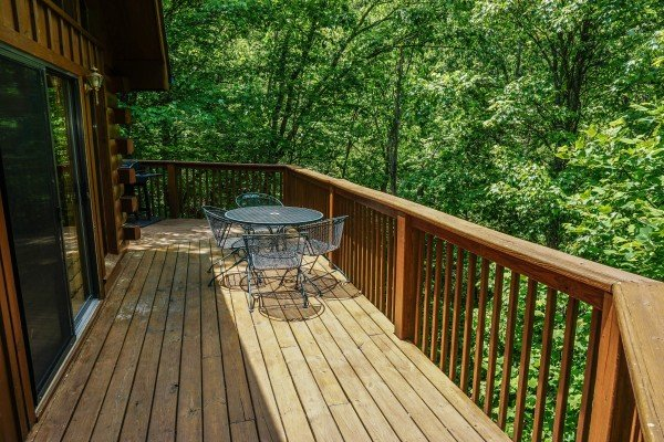 metal patio table and chairs on the deck at angel's place a 2 bedroom cabin rental located in pigeon forge
