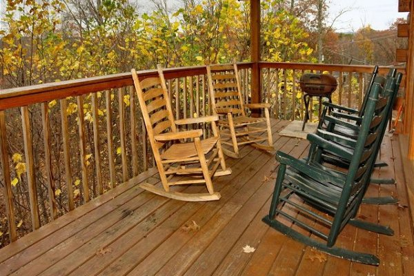 Rocking chairs and a charcoal grill on the deck at Mountain Treehouse, a 4 bedroom cabin rental located in Gatlinburg