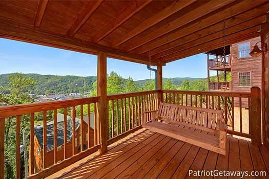 shaded swing on the deck at elk horn lodge a 5 bedroom cabin rental located in gatlinburg