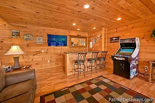Wet bar and arcade game in the game room at Elk Horn Lodge, a 5-bedroom cabin rental located in Gatlinburg