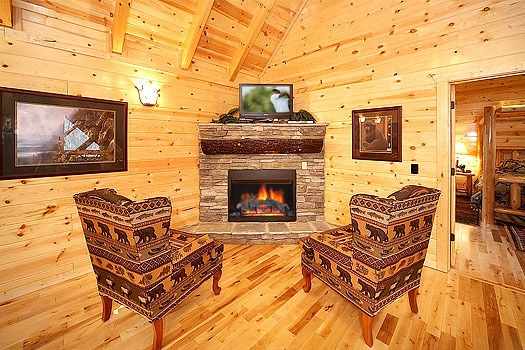 two chairs in front of the stone fireplace in the loft at incredible! a 6 bedroom cabin rental located in gatlinburg