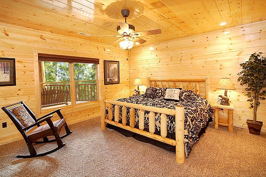 first floor bedroom with king sized bed at incredible! a 6 bedroom cabin rental located in gatlinburg