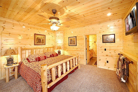 first floor bedroom with king sized bed and attached bathroom at incredible! a 6 bedroom cabin rental located in gatlinburg