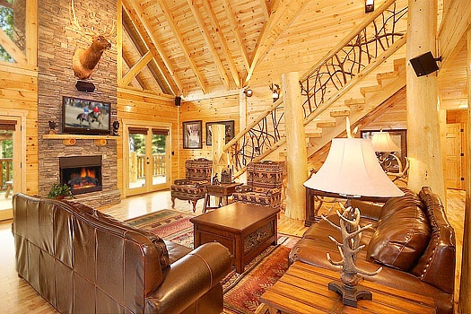 living room with large stone fireplace at incredible! a 6 bedroom cabin rental located in gatlinburg