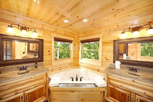 jacuzzi tub between his and her sinks in the main level ensuite at incredible! a 6 bedroom cabin rental located in gatlinburg