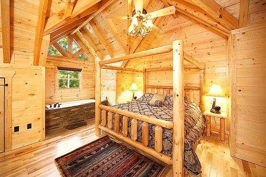 third floor bedroom with canopy log bed and jacuzzi tub at incredible! a 6 bedroom cabin rental located in gatlinburg