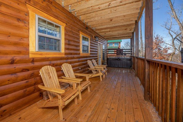 Adirondack chairs on a covered deck at Allstar Pool Lodge, a 4 bedroom cabin rental located in Pigeon Forge