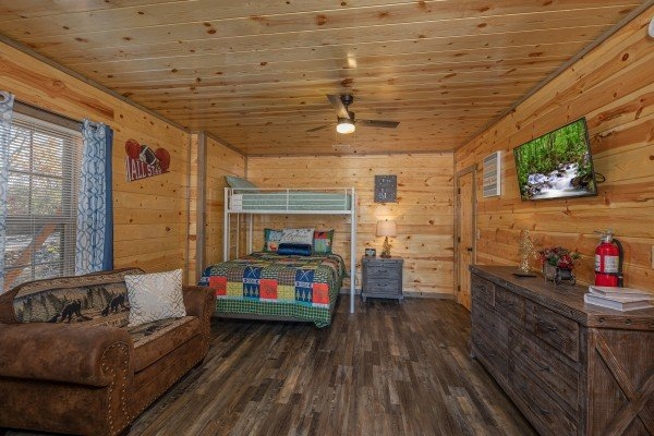 Bunk beds, TV, dresser, and sleeper sofa in a room at Allstar Pool Lodge, a 4 bedroom cabin rental located in Pigeon Forge