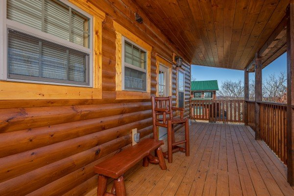 Bench and chair on the deck at Allstar Pool Lodge, a 4 bedroom cabin rental located in Pigeon Forge