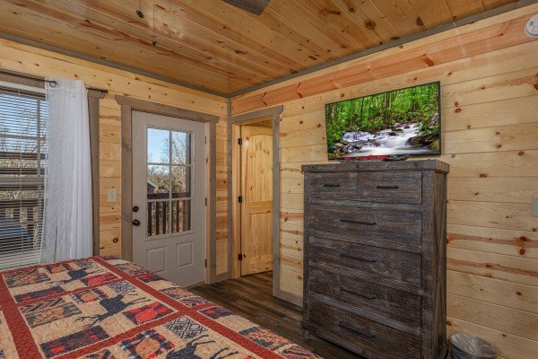 Dresser, TV, and deck access in a bedroom at Allstar Pool Lodge, a 4 bedroom cabin rental located in Pigeon Forge