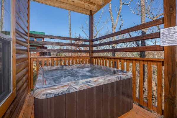 Hot tub on a covered deck at Allstar Pool Lodge, a 4 bedroom cabin rental located in Pigeon Forge