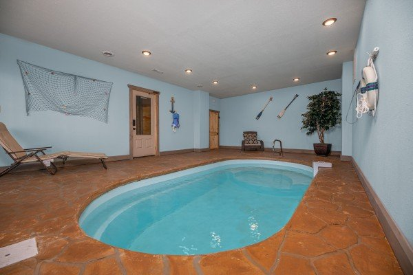 Lounge chair and indoor pool at Allstar Pool Lodge, a 4 bedroom cabin rental located in Pigeon Forge