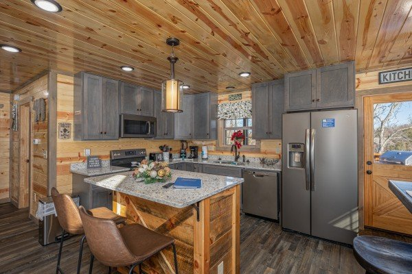 Kitchen with stainless appliances and granite counters at Allstar Pool Lodge, a 4 bedroom cabin rental located in Pigeon Forge